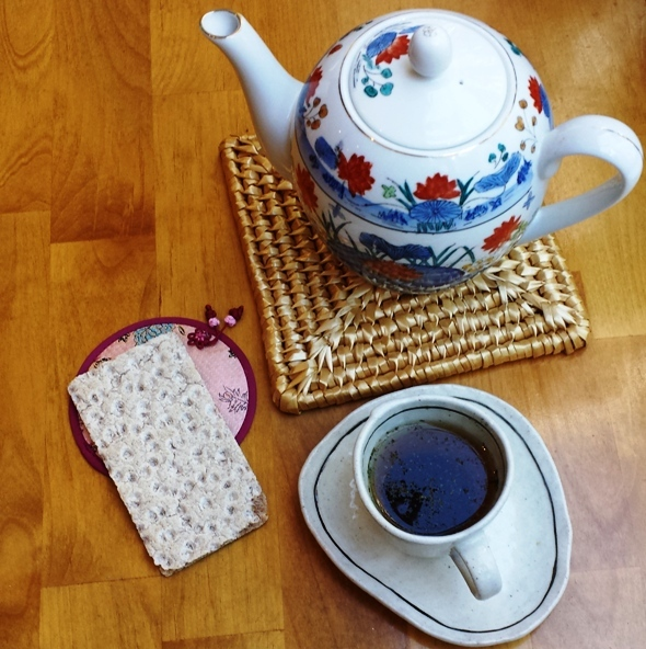 image of tea pot, cup of tea and cracker on table