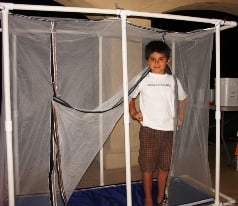 7 year old boy standing inside the bsf propagation unit he built out of mosquito netting and pvc pipe